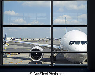 Airport window - Parked aircraft on an airport through the...