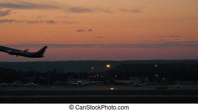 Airport with plane taking off in the dusk - View to the...