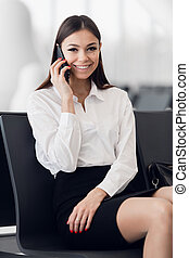 Airport woman on smart phone at gate waiting in terminal. Air travel concept with young casual business woman sitting with talking on the smartphone.
