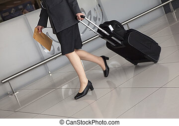 Airport. Woman's legs and travel suitcase