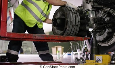 Airport worker checking chassis. Engine and chassis of the passenger airplane under heavy maintenance. Engineer checks the aircraft chassis and engine.