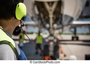 Airport worker in headphones looking at colleagues near passenger plane