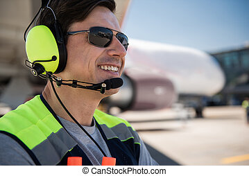 Airport worker in sunglasses and headphones laughing