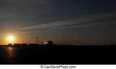 Planes on runway at sunset in airfield take off and prepare...