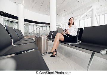 Airport Young female passenger on smart phone and laptop sitting in terminal hall while waiting for her flight. Air travel concept with young casual woman sitting with hand luggage suitcase