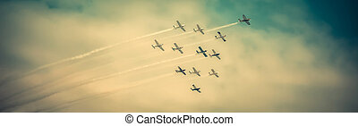 Airshow - Airplanes flying high, in formation, during...