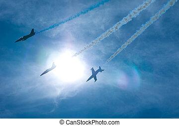Three airplanes performing at an airshow