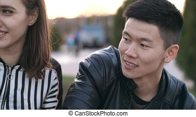 Aisan man talking with friends - Young smiling chinese man...