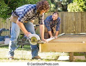 ajudar, coworker, carpinteiro, handheld, meio, olhar, corte, enquanto, madeira, adulto, serra, ele