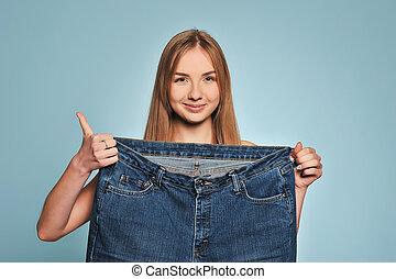 ajustar, mulher jovem, em, solto, calças brim