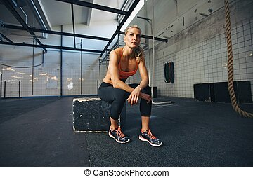 ajustar, mulher jovem, sentando, em, crossfit, ginásio