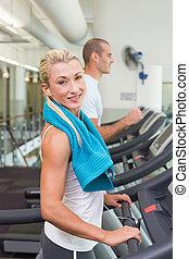 ajustar, par jovem, executando, ligado, treadmills, em, ginásio
