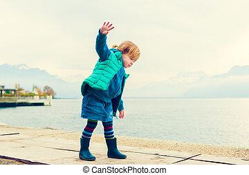 al aire libre, retrato, de, adorable, bebé, niña, de, 2 años, llevando, verde, chaleco, falda mahón, y azul, botas de lluvia