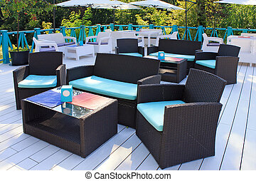 Al fresco cafe with rattan furniture on the garden terrace -...