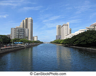 Ala Wai Canel in Waikiki on the island of Oahu in the state of Hawaii. Surrounded by tall buildings.