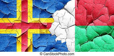 aland islands with Madagascar flag on a grunge cracked wall