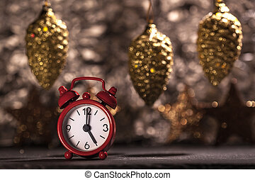 Red alarm clock set to 5 o'clock, Christmas decoration background, shallow depth of field