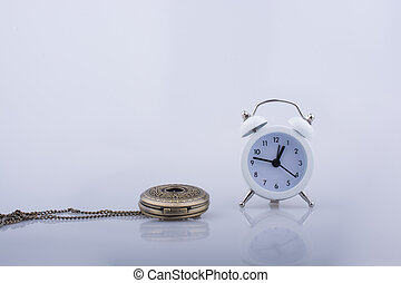 Alarm clock and  a pocket watch side by side