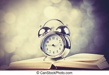 Alarm clock and book. Photo in old color image style.