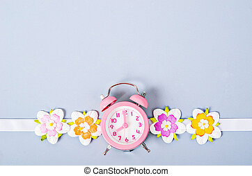 Alarm clock and flower for background.