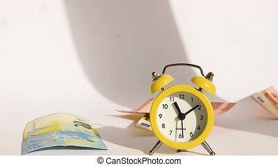 Alarm clock and money flying banknote Euro, concept of business planning and finance