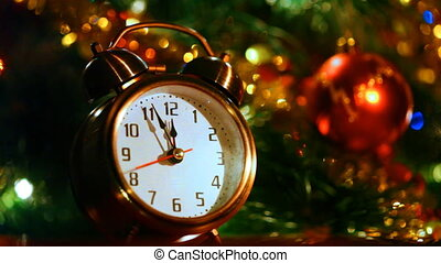 alarm clock at three minutes remaining before New Years in front of festive lights Christmas tree