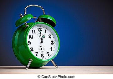 Big green alarm clock on dark blue background