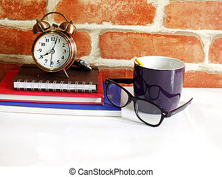 alarm clock cup of coffee and notebook on wooden background