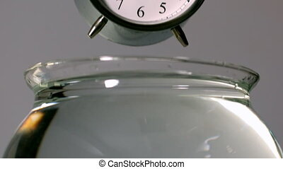 Alarm clock falling into bowl of w