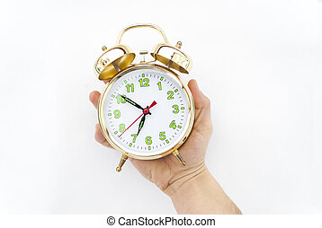 Alarm clock in a hand on a white background