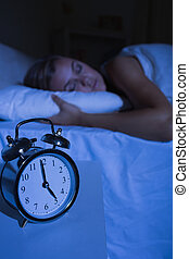 Alarm clock in front of a sleeping woman at night in the...