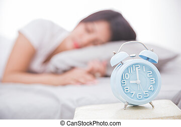 Alarm clock in front woman sleeping on a bed