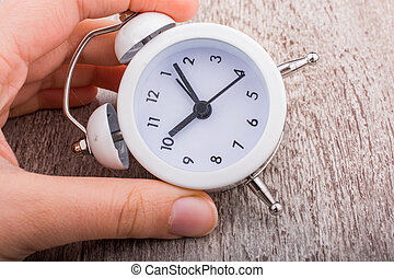 Alarm clock in hand on white background