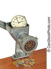 Alarm clock in manual meat grinder and coins on table.