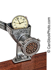 Alarm clock in manual meat grinder on white background.