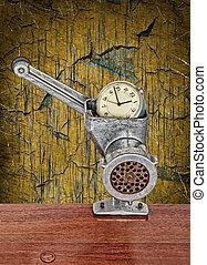 Alarm clock in meat grinder on grunge scratched background.