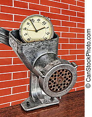 Alarm clock in meat grinder on red brick wall background.