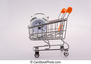 Alarm clock in shopping trolley on white background