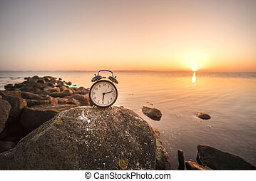Alarm clock in the sunrise by the sea