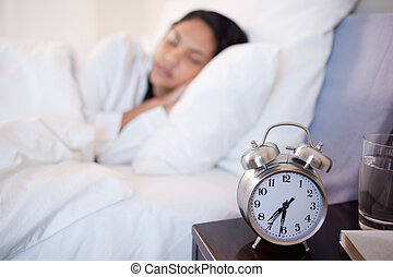 Alarm clock next to woman sleeping in her bed