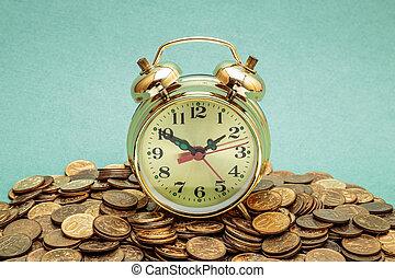 alarm clock on a heap of coins