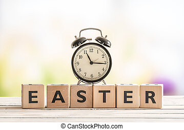 Alarm clock on a wooden easter sign