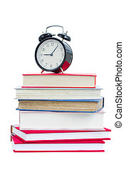 alarm clock on stuck of books