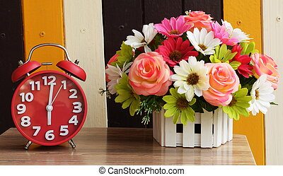 alarm clock on table with flower