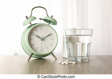 Alarm clock, pills and glass of water on wooden table, close up