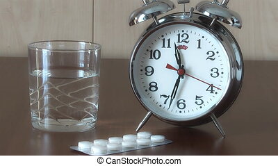 Alarm Clock and Pills on the table, taking pills on schedule
