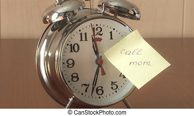 Alarm Clock, - An alarm clock and a yellow note with this...