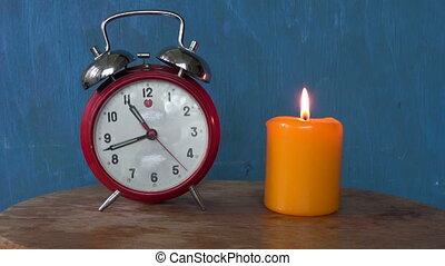 Alarm clock with a burning candle