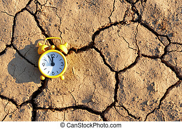 Alarm clock with five minutes before twelve o'clock on arid cracked soil.