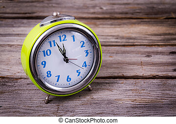 alarm clock with four minutes to twelve o'clock